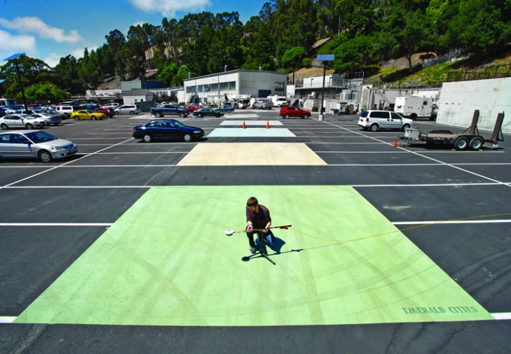 At the Lawrence Berkeley National  Laboratory's cool pavement showcase, research associate Jordan Woods measures solar reflection levels with an albedometer. Credit Lawrence Berkeley National  Laboratory/Roy Kaltschmidt